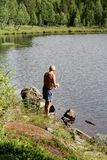 Man fishing by a lake stock images