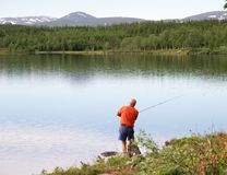 Man fishing by a lake royalty free stock photos