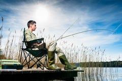 Man fishing at lake sitting on jetty Royalty Free Stock Image