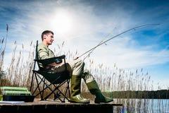 Man fishing at lake sitting on jetty Royalty Free Stock Photos