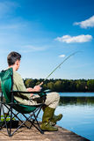 Man fishing at lake sitting on jetty Royalty Free Stock Photography