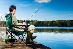 Man fishing at lake sitting on jetty Stock Photos