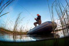 Man fishing on the lake. Split shot of a man fishing from the boat on the lake Royalty Free Stock Photography