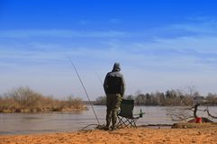 Man fishing in the lake, spring. Spring by the river, a fisherman standing by the water waiting for a bite royalty free stock photography