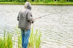 Man fishing in the lake in summer Stock Photo
