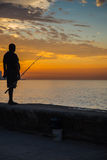 Man fishing at Malecon,  in Havana, Cuba. Havana, Cuba - September 25, 2015: Man fishing at sunset at Malecon,  most popular and famous sea fron promenade in Royalty Free Stock Photo