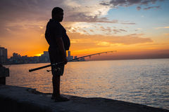 Man fishing at Malecon,  in Havana, Cuba. Havana, Cuba - September 25, 2015: Man fishing at sunset at Malecon,  most popular and famous sea fron promenade in Royalty Free Stock Photography