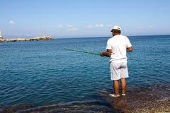 Man fishing in the Mandraki port in Rhodes Stock Photos