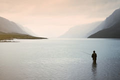 Man fishing in mountain lake Stock Images