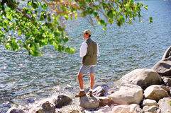Man fishing on mountain lake Stock Photos