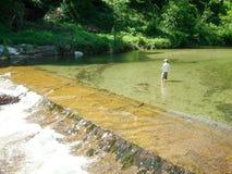 Man fishing on a mountain river over Lugano Stock Image
