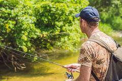 Man fishing on a mountain river with a ultralight spinning using fishing wobblers. He got his hook hooked for something Stock Photography