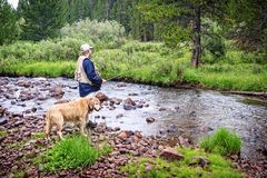 Fisherman by a stream with dog Stock Images