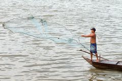 Man fishing near Phnom Penh, Cambodia. This fisherman is getting his nets ready to cast along the shores of the Tonle Sap River near Phnom Penh, Cambodia Royalty Free Stock Photo