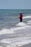 Man Fishing in the Ocean. Man stading in surf fishing on the beach Stock Images