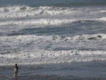 Man Fishing in Ocean Waves Stock Photography