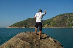 Man fishing off coast Stock Photography