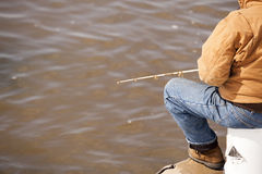 Man fishing off a muddy pier. Man fishing off a muddy pier in brown jacket and jeans Stock Image