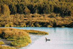 Man Fishing From Old Wooden Fishing Boat In Summer Lake Or River Royalty Free Stock Photography