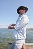 Man Fishing from Pier. Handsome man with sunglasses and sunhat fishing from a pier on a sunny day Stock Image