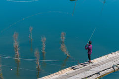 Man fishing from a pier Royalty Free Stock Photo