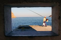 Man fishing at the port of Kamares, Sifnos island, Cyclades, Greece. August 28 2010 Royalty Free Stock Image