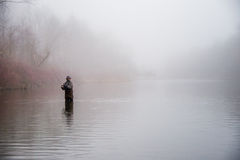 Man fishing in a river. A fisherman wearing waders reels in his lure Royalty Free Stock Photography