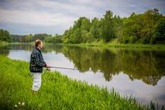 Man fishing. In river, Lithuania green scenery Stock Photo