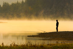 Man Fishing at river shore Stock Photo