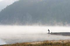 Man fishing at river shore Stock Images