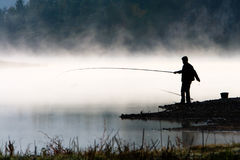 Man fishing at river shore. In the morning Royalty Free Stock Photos