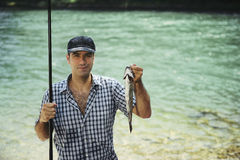 Man fishing on river and showing fish to the camera royalty free stock image