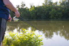Man fishing on river. Man spinning fishing on river in bright sun Royalty Free Stock Photo