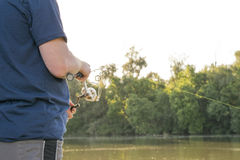 Man fishing on river. Man spinning fishing on river in bright sun Royalty Free Stock Photos