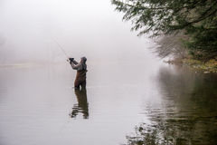 Man fishing in a river. A man wearin waders casts his fishing pole in a river Royalty Free Stock Image