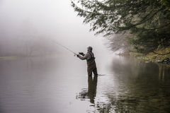 Man fishing in a river. A man wearing waders casts his fishing pole in a river Royalty Free Stock Photos