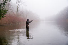 Man fishing in a river. A man wearing waders casts his fishing pole in a river Royalty Free Stock Photo