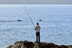 Man fishing from a rock Stock Photography
