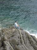 Man fishing from rock Royalty Free Stock Photography