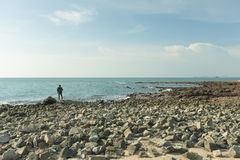 Man fishing at rocky beach Stock Images