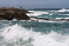 Man fishing at the rocky coast of Brittany Royalty Free Stock Images