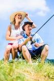 Man with fishing rod angling at lake enjoying hug. By women at his side Royalty Free Stock Images
