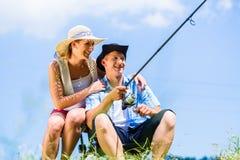 Man with fishing rod angling at lake enjoying hug. By women at his side Royalty Free Stock Photos
