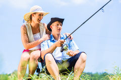 Man with fishing rod angling at lake enjoying hug Stock Image