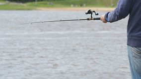 Man is fishing with a rod on background of river stock video footage