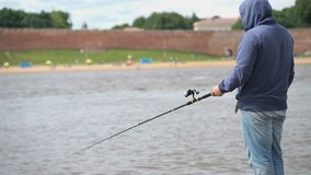 Man is fishing with a rod on background of river stock video