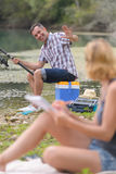 Man with fishing rod enjoying with woman at side Stock Image