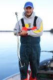 Man With Fishing Rod And Lure. A man out fishing shows the camera the spoon lure he is using to catch fish Royalty Free Stock Photo