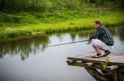 Man fishing. With rod in a pond, summer time Stock Photography