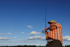 Man Fishing With Rod and Reel. An action shot of man fishing against crisp blue sky Royalty Free Stock Photos